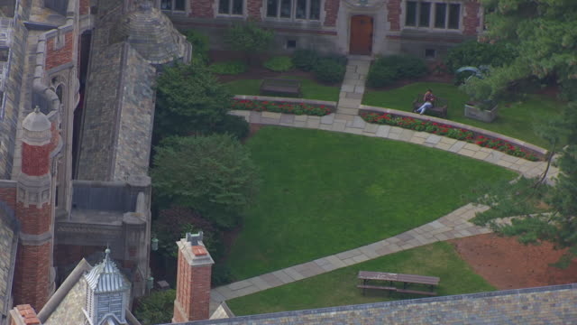 WS AERIAL POV ZO Student using phone while studying on bench inside Yale Law School / New Haven, Connecticut, United States