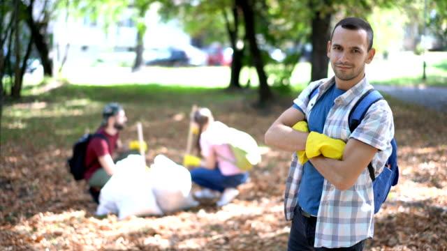 stockvideo's en b-roll-footage met student vrijwilliger glimlachend in de camera en het tonen van de duimen omhoog - armen over elkaar