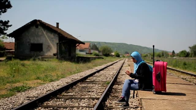 vídeos de stock, filmes e b-roll de estudante, esperando o trem na estação de trem, jovem e moderna garota muçulmana com mochila e mala - vestuário modesto