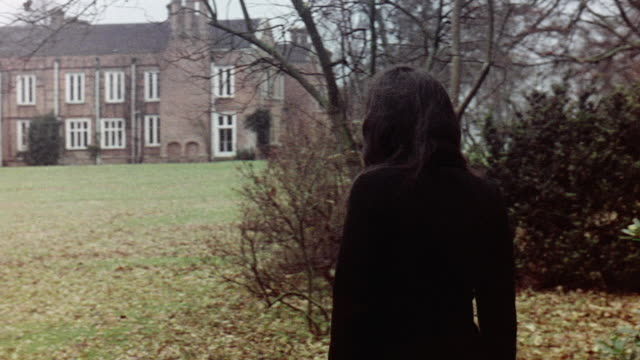 vidéos et rushes de 1970 ts student walking across rural campus towards the coal board staff college building / buckinghamshire, england, united kingdom - 1970