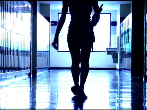vídeos de stock, filmes e b-roll de student walking in school hallway - vista traseira