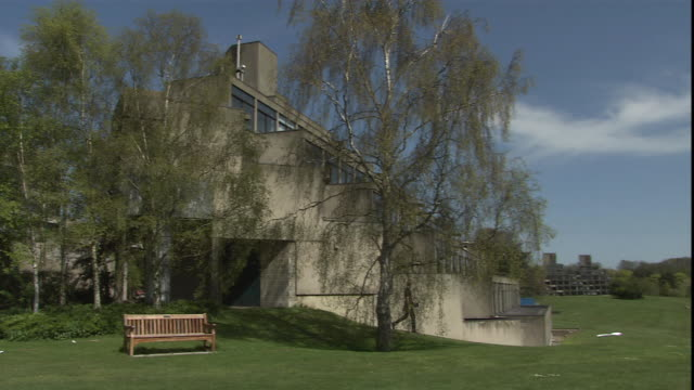 a student walks past a wood campus building at the university of east anglia. - east anglia stock videos & royalty-free footage