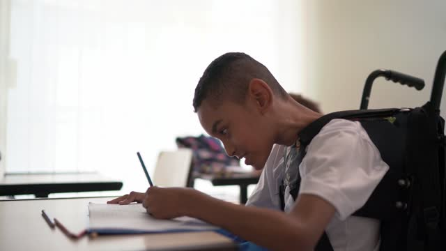 student with disability taking notes during class at school - dedication stock videos & royalty-free footage