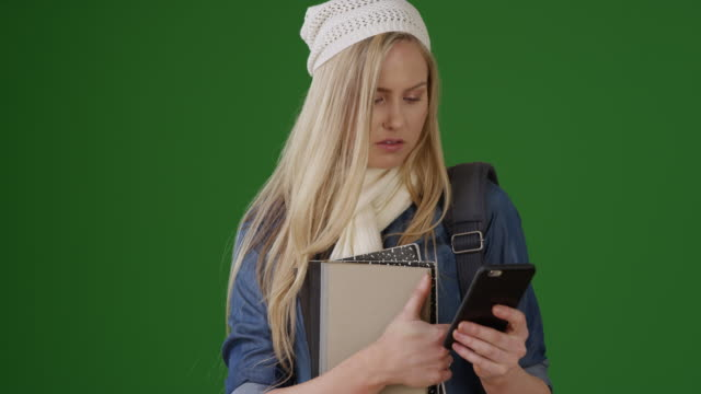 Student with her books and backpack uses her smart phone on green screen