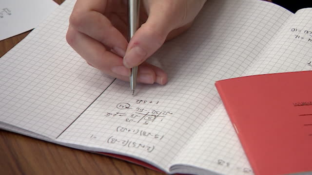 student writing sum in exercise book during school maths lesson, sussex - mathematics stock videos & royalty-free footage