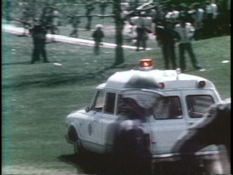 students and guardsmen watch as an ambulance drives across a campus field. - crime or recreational drug or prison or legal trial stock videos & royalty-free footage