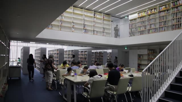 Students and other patrons read at tables in the Tianjin Library.