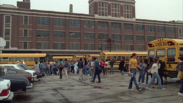 WS Students and school buses in front of large three-story urban school building / USA