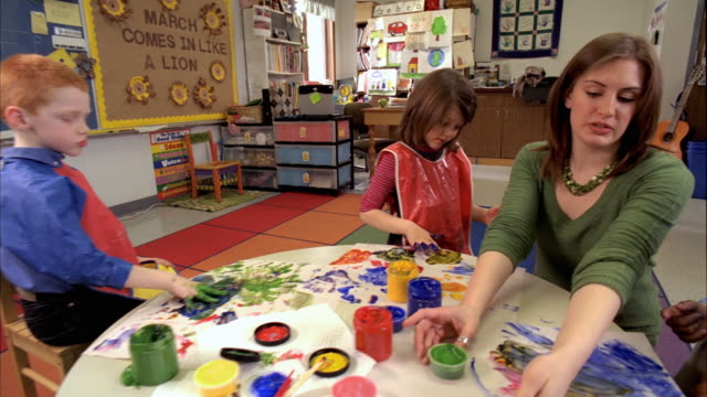 MS Students (5-6) and teacher painting with finger paints, Oshkosh, Wisconsin, USA