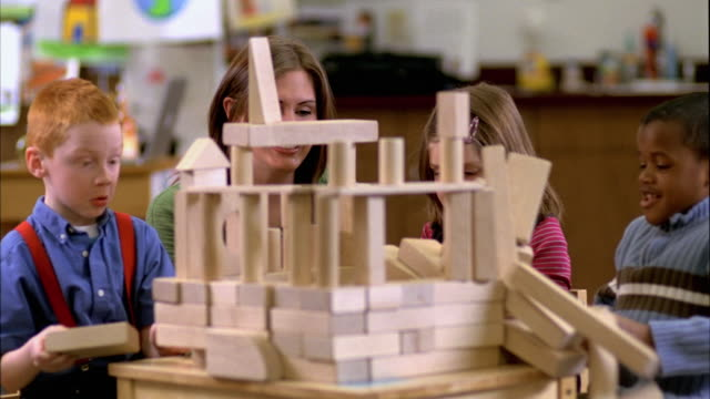 SLO MO MS Students and teacher (5-6) playing with blocks, structure collapses, Oshkosh, Wisconsin, USA