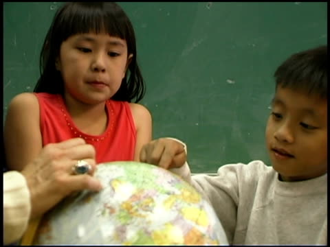 stockvideo's en b-roll-footage met students and teacher pointing at globe - bureauglobe