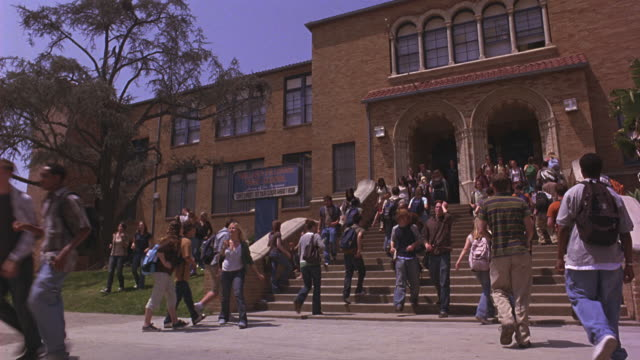 Students and teachers exiting and entering a high school.