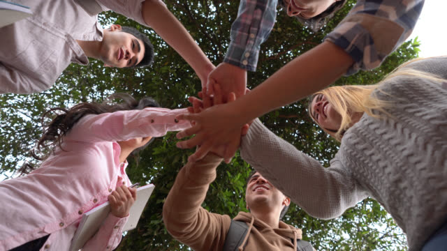 students at college in a huddle and then doing high five - low angle view stock videos & royalty-free footage