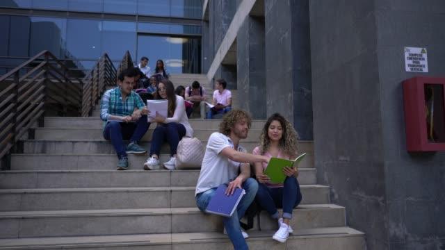 vidéos et rushes de étudiants du collège, assis sur les escaliers en groupes et couples - escalier