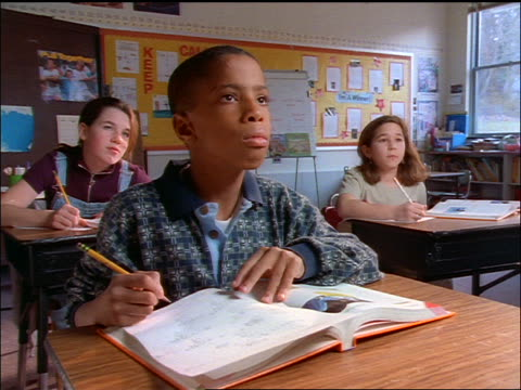 vídeos de stock, filmes e b-roll de students at desks in classrooom / black boy in front row raises hand to give answer - braço humano