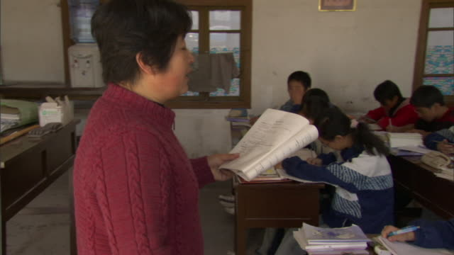 ms pan students at desks in crowded classroom listening to female teacher reading from workbook, weishan, yunnan, china - female high school student stock videos & royalty-free footage