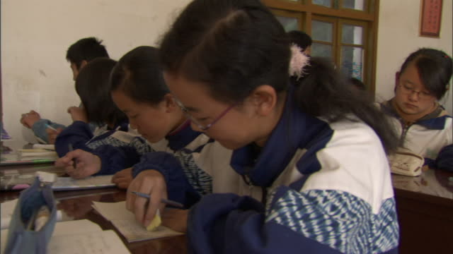 cu pan students at desks in crowded classroom writing in notebooks, weishan, yunnan, china - 試験点の映像素材/bロール