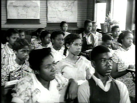 1939 MS students at their desks raising their hands, then one student standing and walking forward / USA