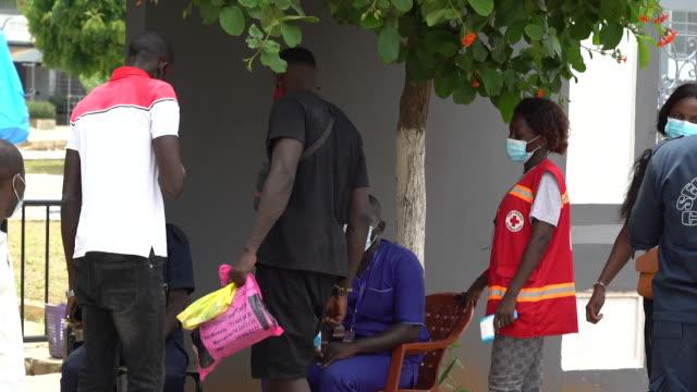 students at university in dakar, senegal, having temperature taken due to coronavirus pandemic - セネガル点の映像素材/bロール
