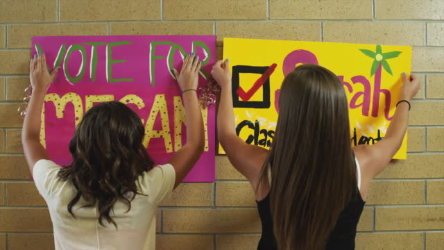 ms zo students (16-17) attaching posters on wall / spanish fork city, utah, usa - poster stock-videos und b-roll-filmmaterial