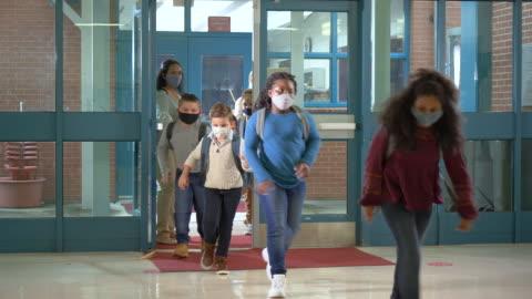 vídeos y material grabado en eventos de stock de los estudiantes regresan a la escuela durante el covid-19, usando máscaras - education