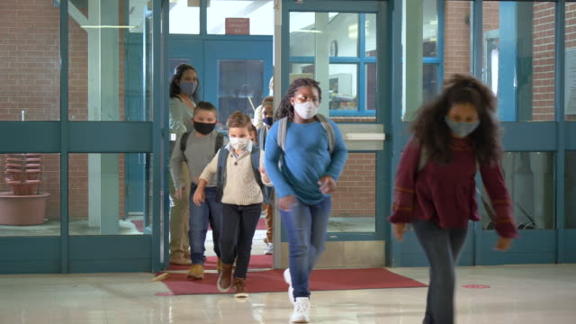students back to school during covid-19, wearing masks - primary school child stock videos & royalty-free footage