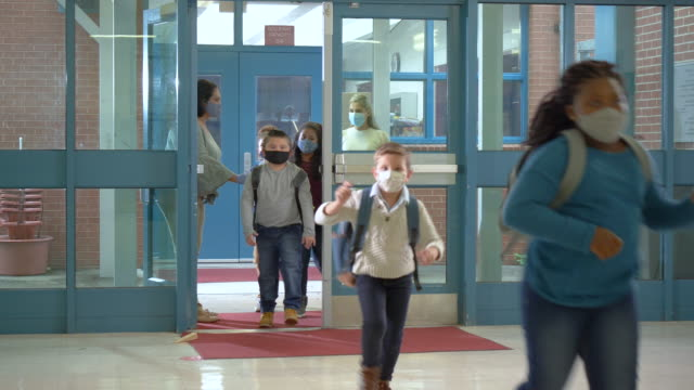 students back to school during covid-19, wearing masks - elementary school stock videos & royalty-free footage