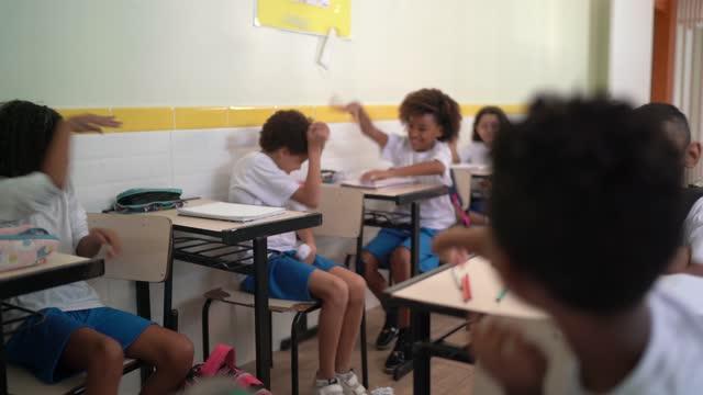 vídeos de stock, filmes e b-roll de alunos lutam contra bola de papel amassada em sala de aula na escola - desarrumado