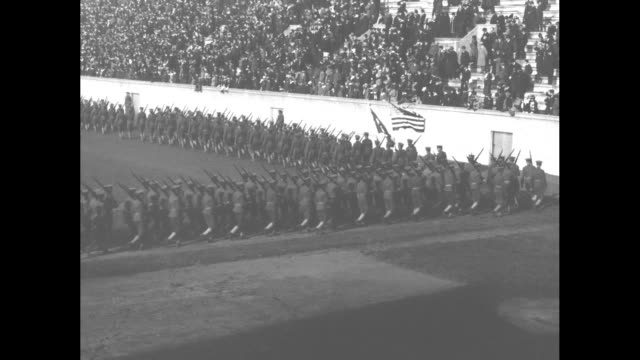 students brigade in uniform march on field in front of stands filled with spectators / vs brigadier general clarence edwards, commander of the... - 戦隊点の映像素材/bロール