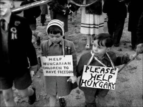 Students campaign for Hungary aid ENGLAND London Hyde Park EXT People in procession with banters etc / Two children in procession with placards PAN...