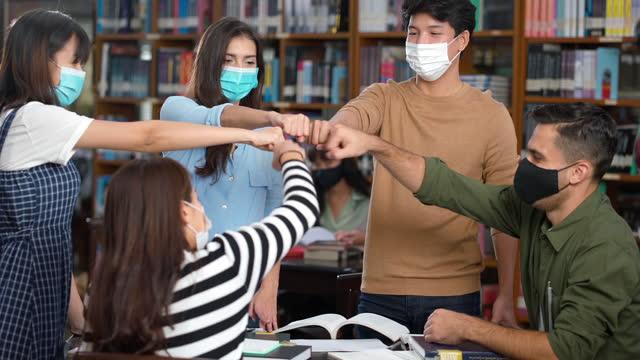 schüler feiern gemeinsam mit neuer normalität und tragen gesichtsmaske in der bibliothek - nur teenager stock-videos und b-roll-filmmaterial