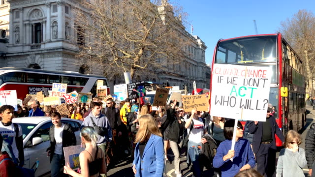 students chant and wave their placards in parliament square during a climate protest on february 15 2019 in london united kingdom thousands of uk... - klima stock-videos und b-roll-filmmaterial