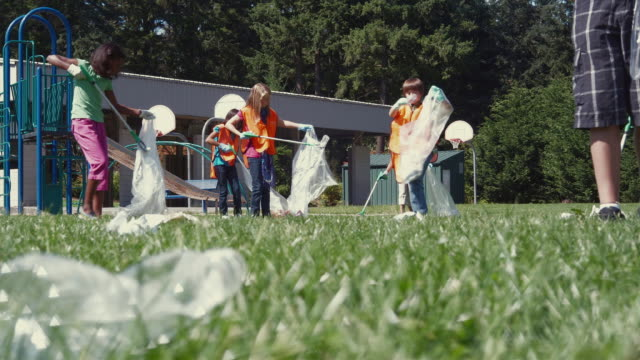 ws r/f students (8-11) cleaning up litter on playground / edmonds, washington, usa - see other clips from this shoot 1750 stock videos and b-roll footage