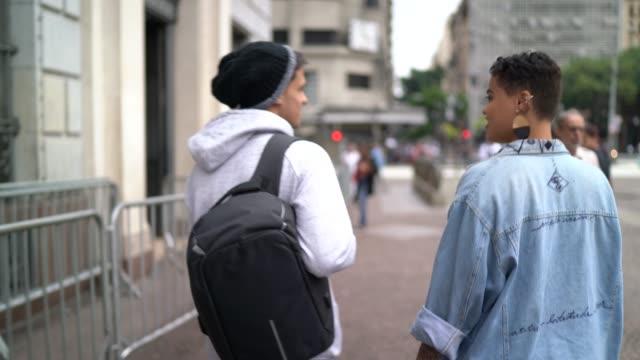 vídeos de stock, filmes e b-roll de casal de estudantes andando na rua - rua principal rua