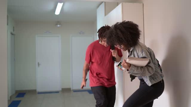 stockvideo's en b-roll-footage met studenten die/het vieren in de universitaire gang dansen - 20 24 jaar