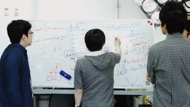 students discussing theorems on whiteboard - 大学点の映像素材/bロール