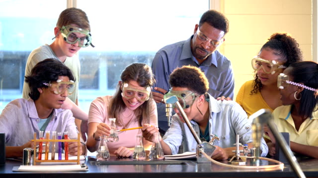 students doing chemistry experiment as teacher watches - 16 17 years stock videos & royalty-free footage