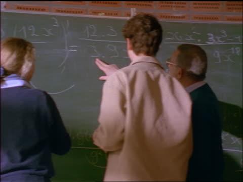 rear view 2 students doing math problems on chalkboard / male teacher helps them - mathematikstunde stock-videos und b-roll-filmmaterial