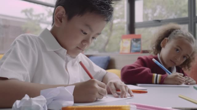 students drawing at table in school - 6歳から7歳点の映像素材/bロール