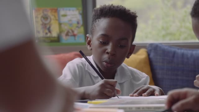 vidéos et rushes de students drawing in books at table - niveau primaire