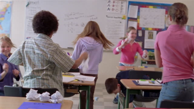 Students engaging in paper fight while teacher is away / throwing paper at camera / Gorham, Maine