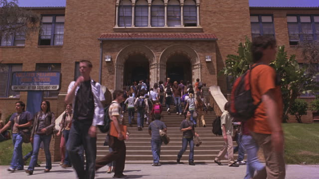 Students entering and exiting a school.