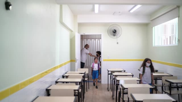 vídeos de stock e filmes b-roll de students entering classroom greeting teacher and avoiding handshakes and using face mask - américa latina