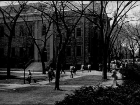 Students faculty people walking sidewalks of Harvard Yard