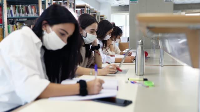 gli studenti si sono concentrati sullo studio in una biblioteca pubblica - university video stock e b–roll