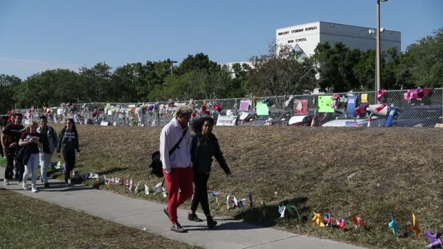 Students from Marjory Stoneman Douglas High School walk out of school to honor the memories of 17 classmates that were killed during a mass shooting...