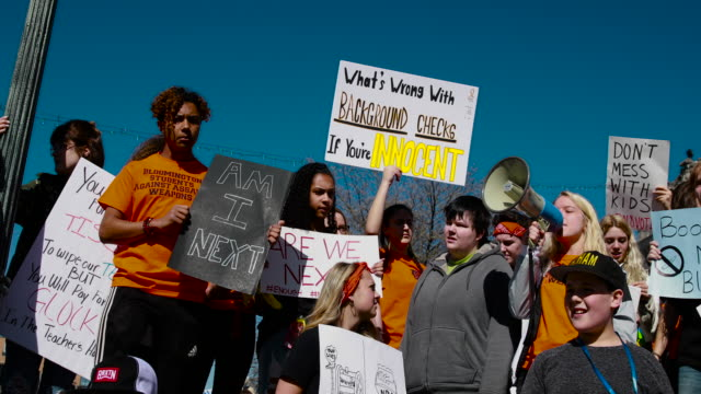 students from schools in bloomington, indiana participate in a rally for national school walkout day to protest school violence on april 20, 2018 in... - gun violence protest stock videos & royalty-free footage