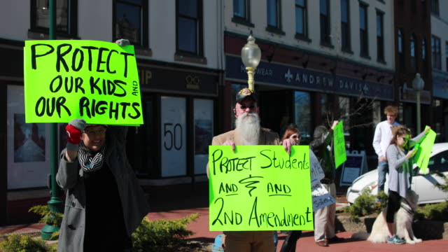 vídeos de stock e filmes b-roll de students from schools in bloomington indiana participate in a rally for national school walkout day to protest school violence on april 20 2018 in... - comício político