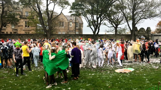 students from st andrews university indulge in a tradition of covering themselves with foam to honour the 'academic family' on the lower college lawn... - st. andrews scotland stock videos & royalty-free footage
