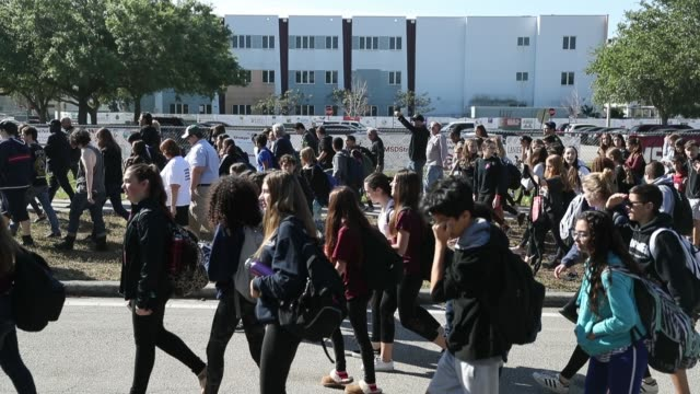 students from westglades middle school walk past the freshman building at marjory stoneman douglas high school after walking out of their school to... - sciopero video stock e b–roll